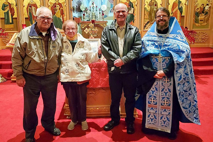 Fr Innocent poses with Stephen, Jean Anne & their son Brian for a photo.